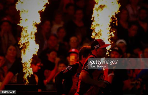 Aaron Finch and Brad Hogg of the Renegades run onto the field with their teammates through flames during the Big Bash League match between the...