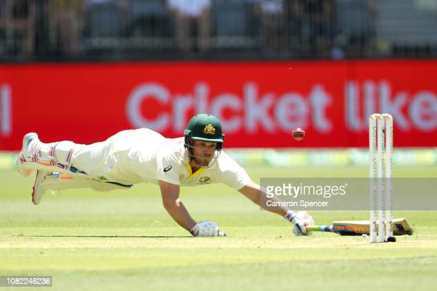 Aaron Finch of Australia avoids a run-out during day one of the second match in the Test series between Australia and India at Perth Stadium on...