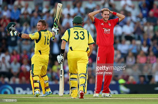 Aaron Finch of Australia celebrates his century as Stuart Broad of England looks on during the 1st NatWest Series T20 match between England and...
