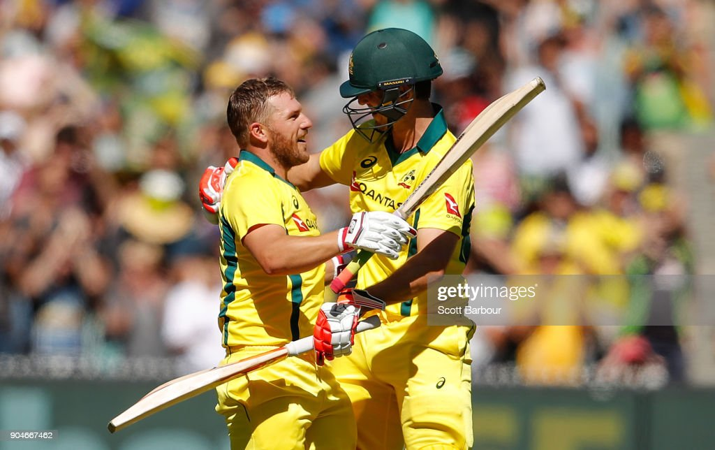 Aaron Finch of Australia celebrates reaching his century with Mitchell Marsh during game one of the One Day International Series between Australia and England at Melbourne Cricket Ground on January 14, 2018 in Melbourne, Australia.