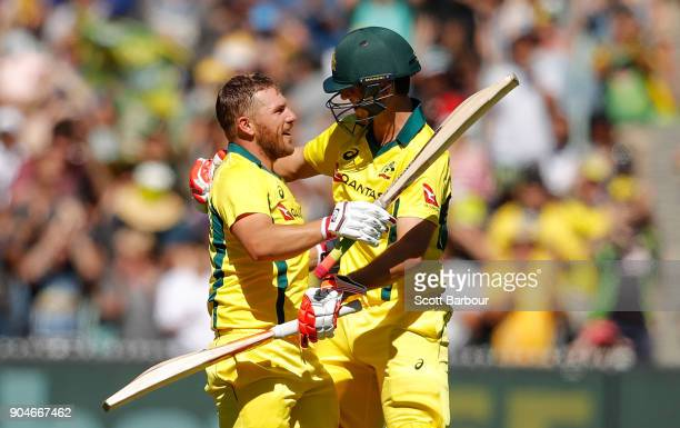 Aaron Finch of Australia celebrates reaching his century with Mitchell Marsh during game one of the One Day International Series between Australia...