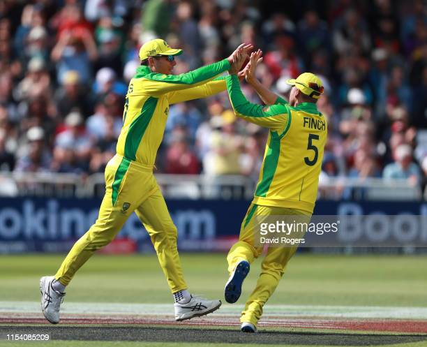 Aaron Finch of Australia celebrates with team mate Pat Cummins after catching Nicholas Pooran during the Group Stage match of the ICC Cricket World...