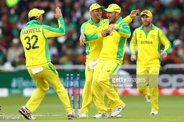 Aaron Finch of Australia celebrates with Usman Khawaja and Glenn Maxwell after running out Soumya Sarkar of Bangladesh during the Group Stage match...