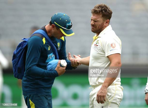 Aaron Finch of Australia is seen to by Australian Team Physiotherapist David Beakley after he was struck on the hand by a delivery from Ishant Sharma...