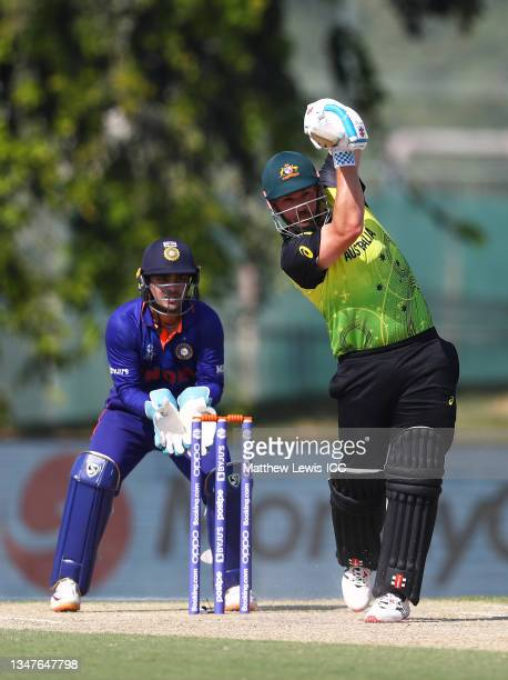 Aaron Finch of Australia plays a shot as Ishan Kishan of India looks on during the India and Australia warm Up Match prior to the ICC Men's T20 World...