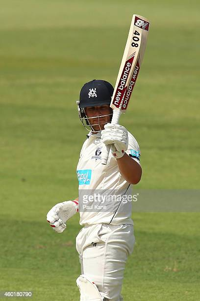Aaron Finch of Victoria raises his bat after reaching is half century during day one of the Sheffield Shield match between Western Australia and...