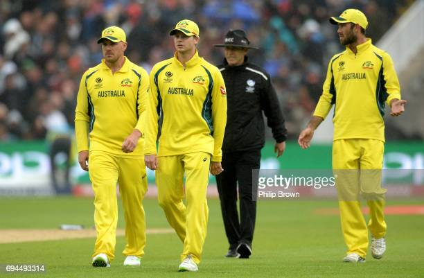 Aaron Finch Steve Smith and Glenn Maxwell of Australia leave the field as the rain falls during the ICC Champions Trophy match between England and...