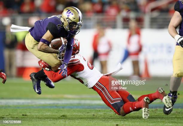 Aaron Fuller of the Washington Huskies is tackled by Julian Blackmon of the Utah Utes during the Pac 12 Championship game at Levi's Stadium on...