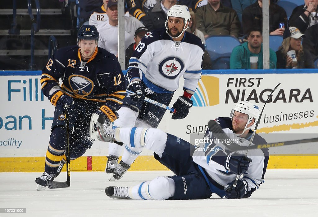 Aaron Gagnon #21 of the Winnipeg Jets gets tripped up in front of Kevin Porter #12 of the Buffalo Sabres at First Niagara Center on April 22, 2013 in Buffalo, New York. Winnipeg defeated Buffalo, 2-1.