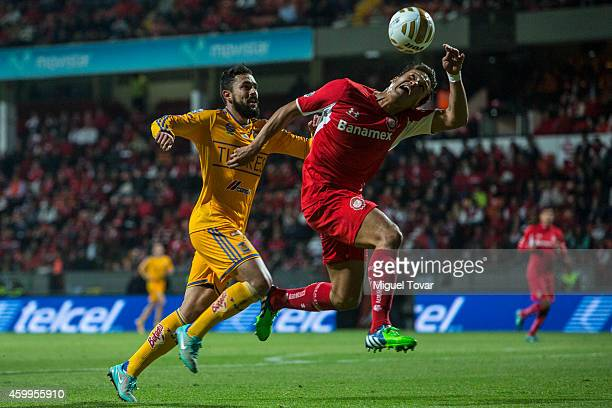 Aaron Galindo of Toluca heads the ball as Herculez Gomez of Tigres looks during a semifinal first leg match between Toluca and Tigres UANL as part of...
