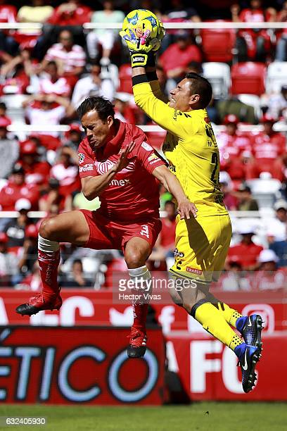 Aaron Galindo of Toluca struggles for the ball with Moises Muñoz goalkeeper of Chiapas during a match between Toluca and Chiapas as part of the...