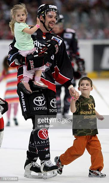 Aaron Gavey of Cologne celebrates with his children after winning the DEL Bundesliga play off quarter final game between Cologne Haie and ERC...