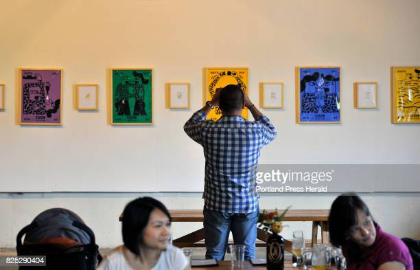 Aaron Gong of Boston photographs the work of artist Keith Shore at the opening exhibition at Oxbow Brewery Saturday August 20 2016