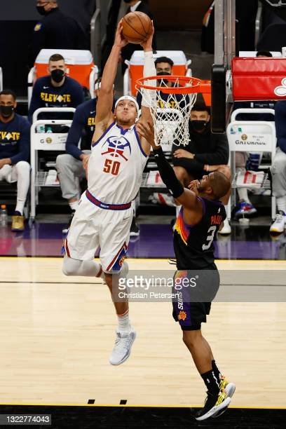 Aaron Gordon of the Denver Nuggets slam dunks the ball over Chris Paul of the Phoenix Suns during the first half in Game Two of the Western...