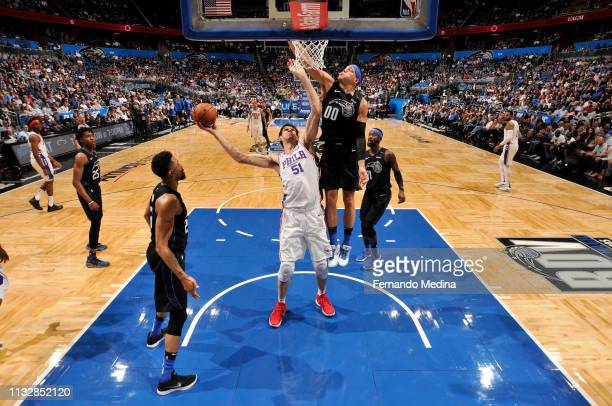 Aaron Gordon of the Orlando Magic blocks against Boban Marjanovic of the Philadelphia 76ers on March 25 2019 at Amway Center in Orlando Florida NOTE...