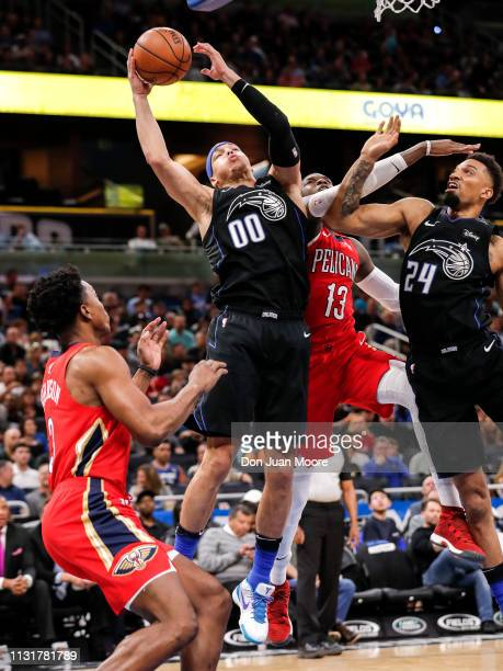 Aaron Gordon of the Orlando Magic goes up for a rebound over Stanley Johnson and Cheick Diallo of the New Orlean Pelicans during the game at the...