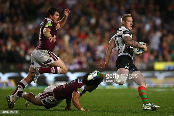 Aaron Gray of the Rabbitohs evades the tackle of Josh Starling and Jorge Taufua of the Eagles during the round 22 NRL match between the Manly Sea...