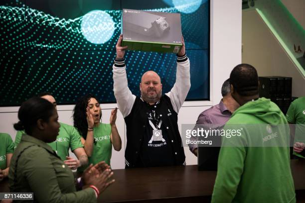 Aaron Greenberg global manager for Xbox at Microsoft Corp holds up an Xbox One X game console before presenting it to the first customer in the...