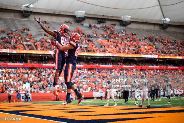 Aaron Hackett celebrates his touchdown reception with Taj Harris of the Syracuse Orange during the first quarter against the Holy Cross Crusaders at...