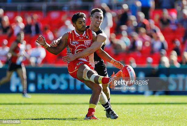 Aaron Hall of the suns gets a kick away during the round 15 AFL match between the Gold Coast Suns and the St Kilda Saints at Metricon Stadium on July...