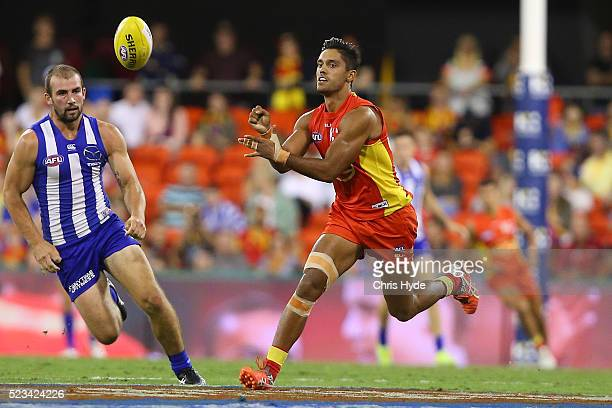 Aaron Hall of the Suns handballs during the round five AFL match between the Gold Coast Suns and the North Melbourne Kangaroos at Metricon Stadium on...