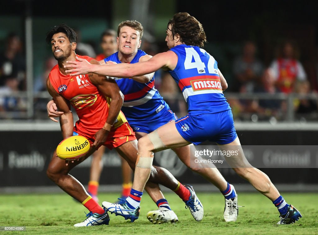 Aaron Hall of the Suns handballs whilst being tackled by Jackson Macrae and Liam Picken of the Bulldogs during the round 18 AFL match between the Western Bulldogs and the Gold Coast Suns at Cazaly's Stadium on July 22, 2017 in Cairns, Australia.
