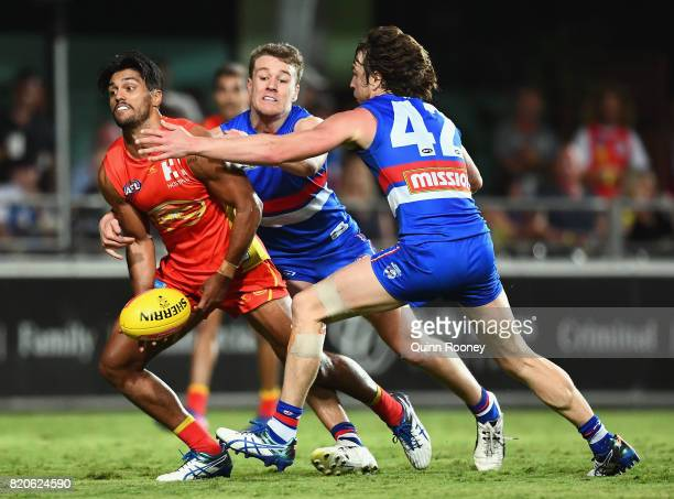 Aaron Hall of the Suns handballs whilst being tackled by Jackson Macrae and Liam Picken of the Bulldogs during the round 18 AFL match between the...