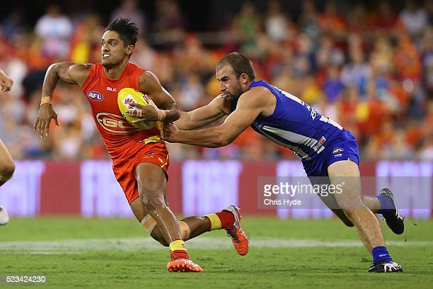 Aaron Hall of the Suns is tackled by Ben Cunnington of the Kangaroos during the round five AFL match between the Gold Coast Suns and the North...