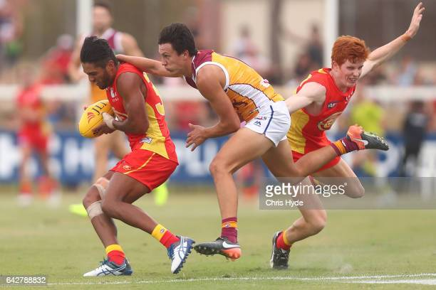 Aaron Hall of the Suns is tackled during the 2017 JLT Community Series match at Broadbeach Sports Centre on February 19 2017 in Gold Coast Australia