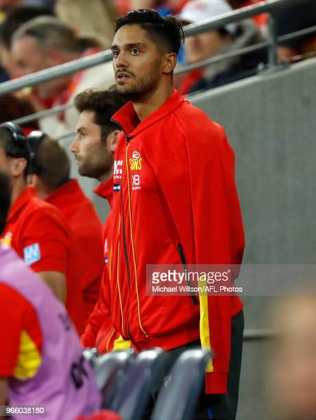 Aaron Hall of the Suns looks on with his arm in a sling during the 2018 AFL round 11 match between the Gold Coast Suns and the Geelong Cats at...