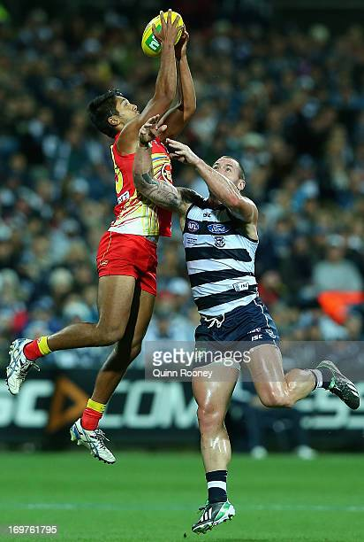 Aaron Hall of the Suns marks over the top of Josh Hunt of the Cats during the round ten AFL match between the Geelong Cats and the Gold Coast Suns at...