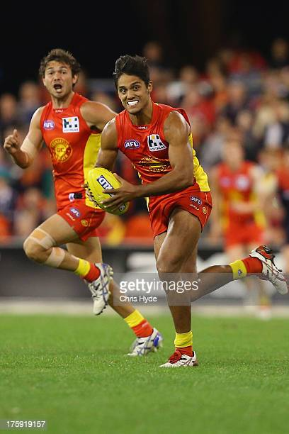 Aaron Hall of the Suns runs the ball during the round 20 AFL match between the Gold Coast Suns and the Melbourne Demons at Metricon Stadium on August...