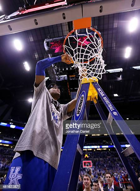 Aaron Harrison of the Kentucky Wildcats cuts the net after defeating the Michigan Wolverines 75 to 72 in the midwest regional final of the 2014 NCAA...