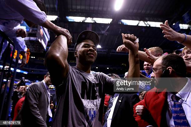 Aaron Harrison of the Kentucky Wildcats high fives fans when leaving the court after defeating the Michigan Wolverines 75 to 72 in the midwest...