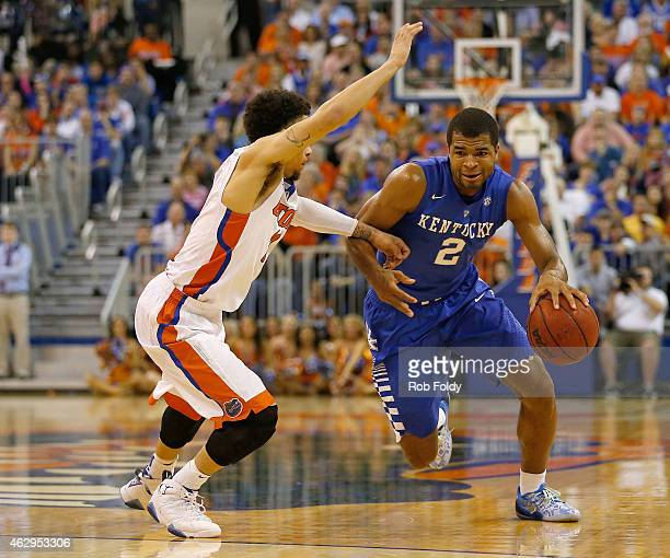 Aaron Harrison of the Kentucky Wildcats is defended by Chris Chiozza of the Florida Gators during the second half of the game at the Stephen C...