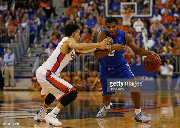 Aaron Harrison of the Kentucky Wildcats is defended by Chris Chiozza of the Florida Gators during the game at the Stephen C O'Connell Center on...