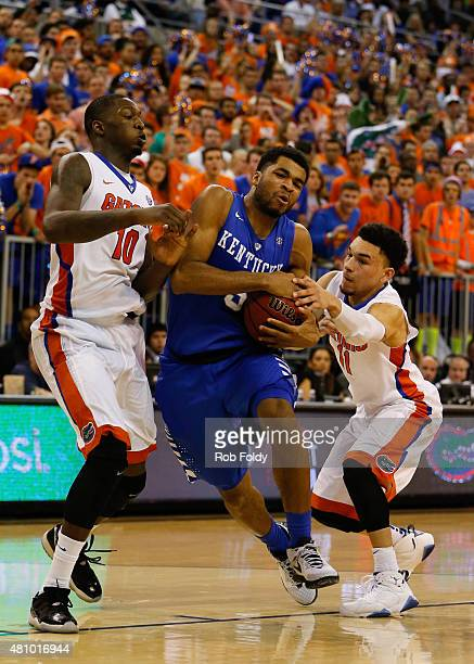 Aaron Harrison of the Kentucky Wildcats is defended by Dorian FinneySmith and Chris Chiozza of the Florida Gators during the game at the Stephen C...