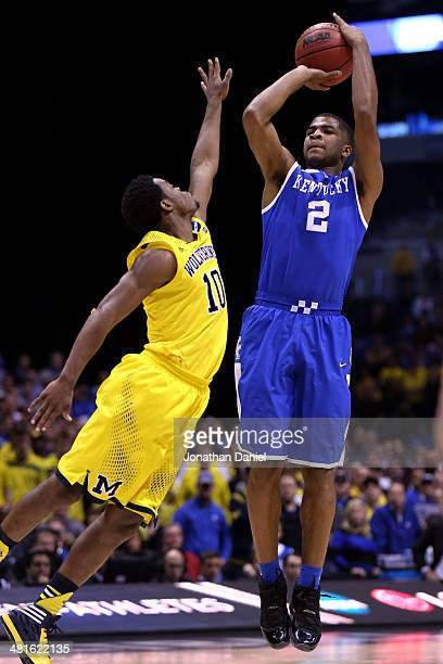 Aaron Harrison of the Kentucky Wildcats shoots the ball against Derrick Walton Jr #10 of the Michigan Wolverines in the second half during the...