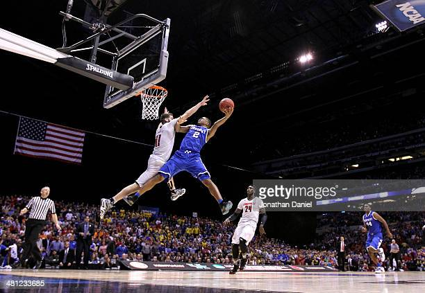 Aaron Harrison of the Kentucky Wildcats shoots the ball over Luke Hancock of the Louisville Cardinals during the regional semifinal of the 2014 NCAA...