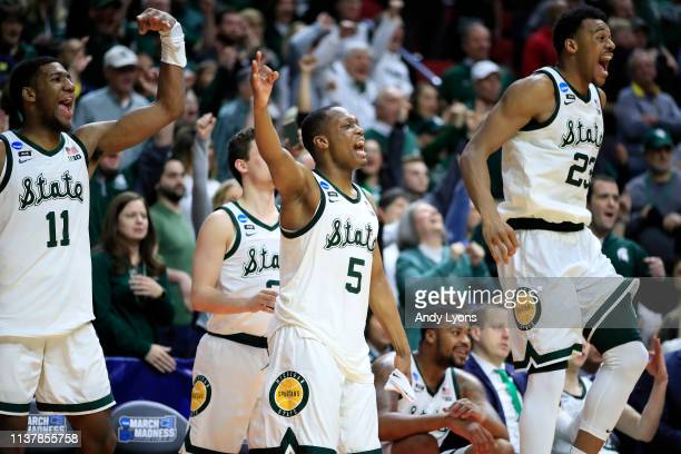 Aaron Henry, Cassius Winston and Xavier Tillman of the Michigan State Spartans celebrate from the bench against the Minnesota Golden Gophers during...