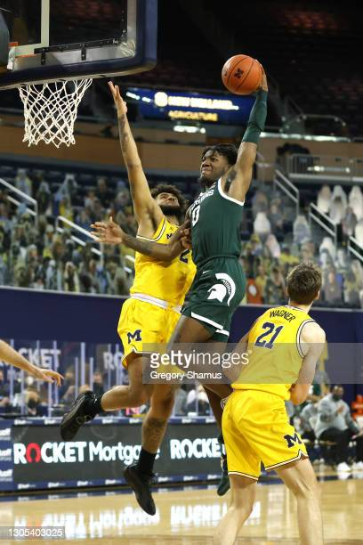 Aaron Henry of the Michigan State Spartans dunks past Isaiah Livers of the Michigan Wolverines during the first half at Crisler Arena on March 04,...