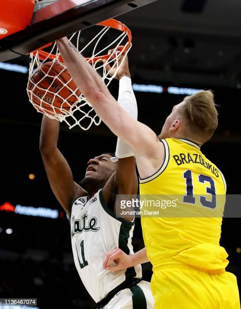 Aaron Henry of the Michigan State Spartans dunks the ball past Ignas Brazdeikis of the Michigan Wolverines in the second half during the championship...