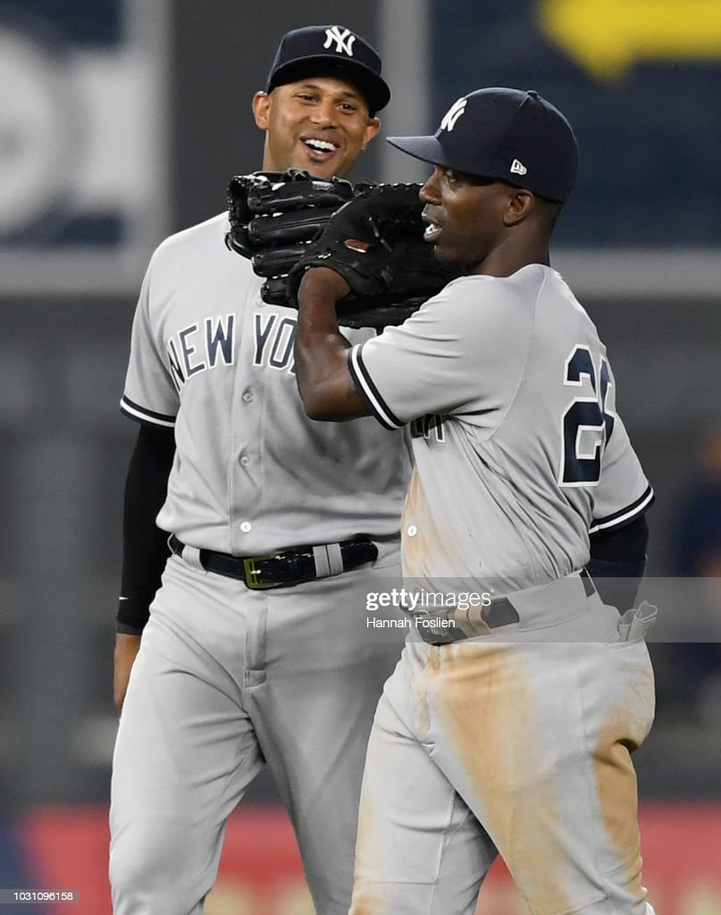 Aaron Hicks #31 and Andrew McCutchen #26 of the New York Yankees celebrate defeating the Minnesota Twins 7-2 after the game on September 10, 2018 at Target Field in Minneapolis, Minnesota.