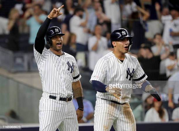 Aaron Hicks and Gleyber Torres of the New York Yankees celebrate after they both scored off a single from teammate Mike Tauchman in the seventh...