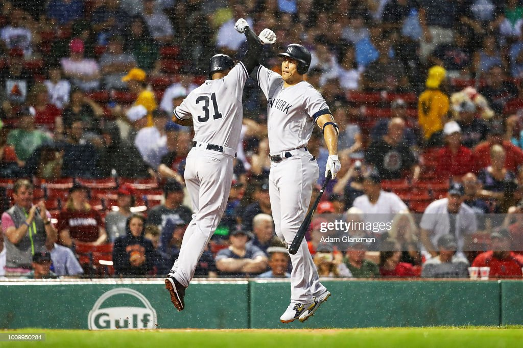 Aaron Hicks #31 high fives Giancarlo Stanton #27 of the New York Yankees after hitting a solo home run in the second inning of a game against the Boston Red Sox at Fenway Park on August 2, 2018 in Boston, Massachusetts.