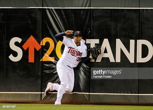 Aaron Hicks of the Minnesota Twins hits the outfield wall after making a catch in center field of the ball hit by Mike Zunino of the Seattle Mariners...