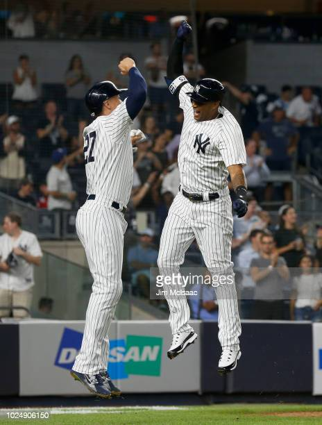 Aaron Hicks of the New York Yankees celebrates his eighth inning two run home run against the Chicago White Sox with teammate Giancarlo Stanton at...