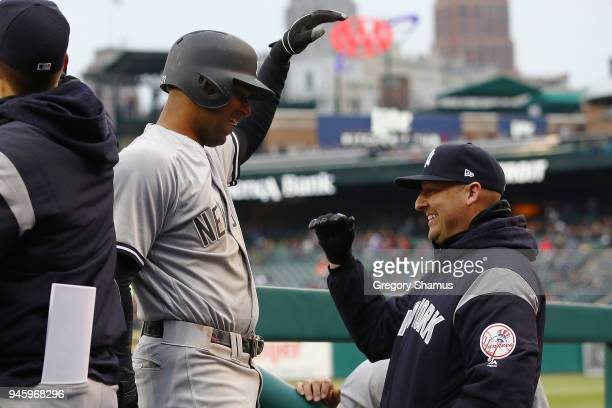 Aaron Hicks of the New York Yankees celebrates his second inning inside the park home run with bench coach Josh Bard while playing the Detroit Tigers...