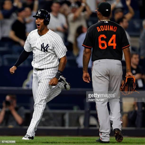 Aaron Hicks of the New York Yankees celebrates rounding third base on a 3run home run by Matt Holliday of the New York Yankees off of Jayson Aquino...