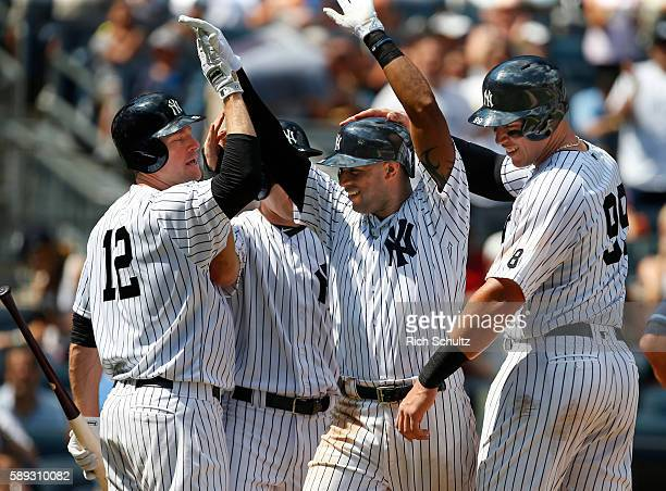 Aaron Hicks of the New York Yankees is congratulated by Chase Headley Jacoby Ellsbury and Aaron Judge after he hit a three run home run in during the...